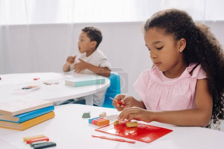 selective focus of african american kid with plasticine sculpturing figure in classroom