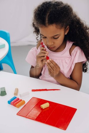 african american kid with plasticine in hands sculpturing figure at table