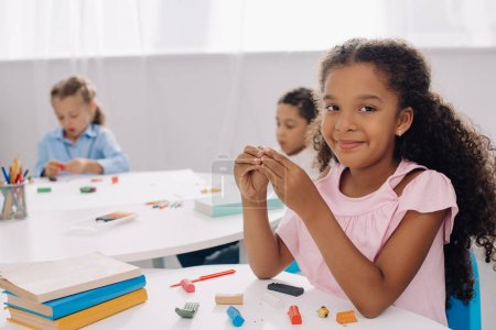 selective focus of smiling african american kid with plasticine in classroom