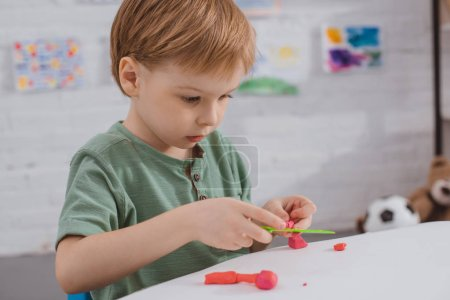 focused boy with colorful plasticine sculpturing figure at table in room