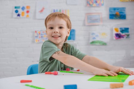 portrait of smiling boy sitting at table with colorful plasticine for sculpturing in room