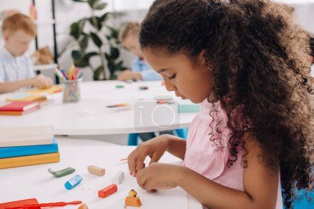 selective focus of african american kid with plasticine sculpturing figure at table in classroom