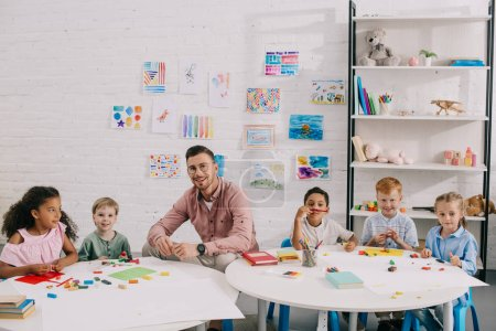 smiling teacher and multiethnic kids sitting at table with colorful plasticine in classroom