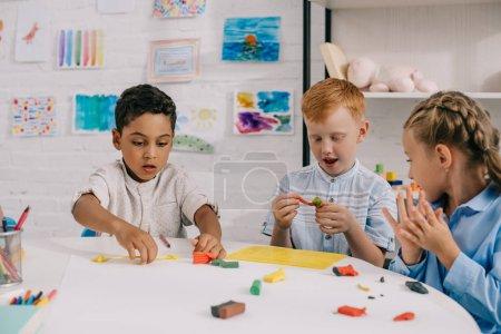 Photo pour Portrait de mignons enfants d'âge préscolaire multiethnique sculptant des figures avec de la plasticine en classe - image libre de droit
