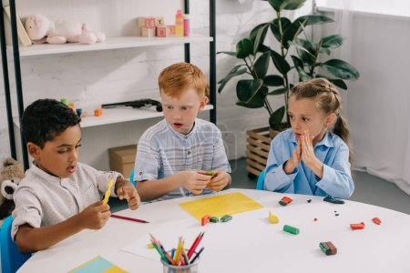 portrait of cute multiethnic preschoolers sculpturing figures with plasticine in classroom
