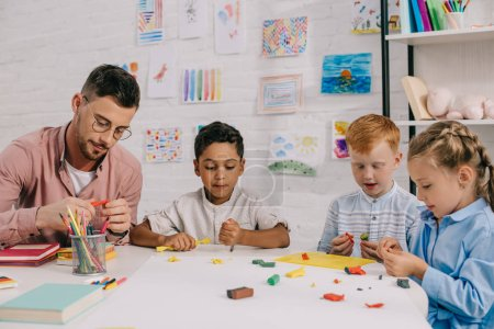 multiracial preschoolers and teacher with plasticine sculpturing figures at table in classroom
