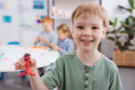 Photo for Selective focus of happy kid showing plasticine figure in hand with classmates behind in classroom - Royalty Free Image
