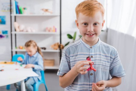 selective focus of smiling red hair boy with figure made of plasticine and classmate drawing picture at table in classroom