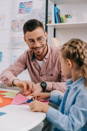 smiling teacher and cute preschooler cutting papers with scissors att able in classroom