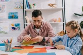 portrait of teacher and cute preschooler cutting papers with scissors att able in classroom