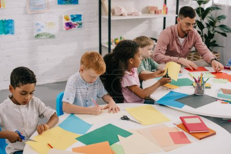teacher and multicultural preschoolers cutting colorful papers with scissors in classroom