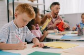selective focus of teacher and multiracial preschoolers with colorful papers making paper applique in classroom