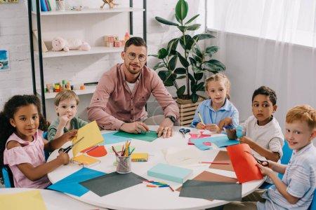 Photo pour Enseignant masculin et enfants d'âge préscolaire multiracial assis à table avec des papiers colorés dans la salle de classe - image libre de droit