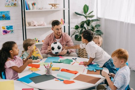 male teacher with soccer ball and multiracial preschoolers sitting at table with colorful papers in classroom