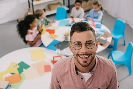 selective focus of smiling teacher in eyeglasses and interracial kids at table in classroom