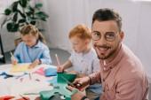 selective focus of smiling teacher and preschoolers making paper applique in classroom