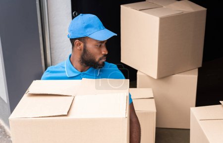 high angle view of african american delivery man holding box near storage