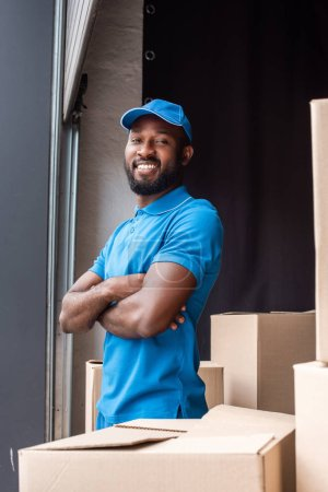 african american delivery man standing with crossed arms near boxes and looking at camera