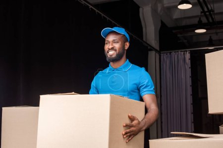 smiling african american delivery man holding box near storage