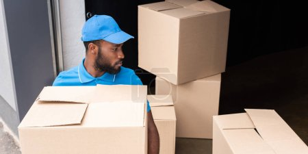 african american delivery man holding box near storage