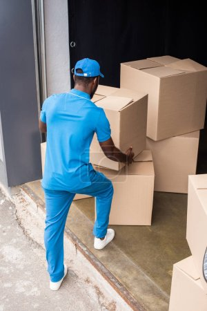 back view of african american delivery man putting boxes on pile