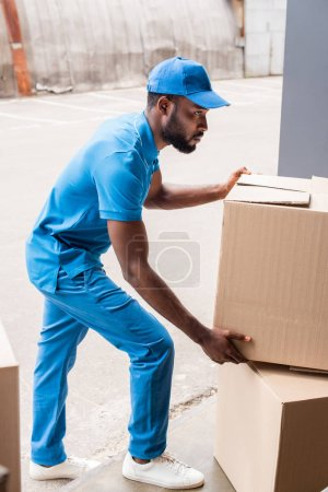 side view of african american delivery man putting boxes on pile