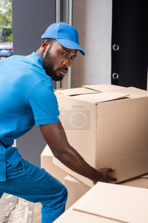 african american delivery man putting boxes on pile