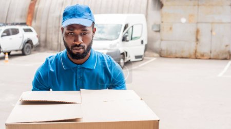 african american delivery man carrying big box with cars on background