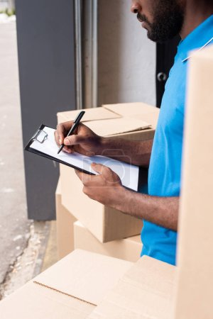 cropped image of african american delivery man writing something to clipboard