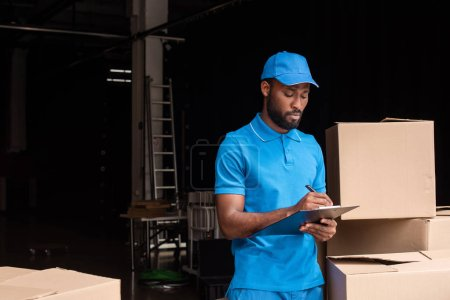 african american delivery man writing something to clipboard near boxes