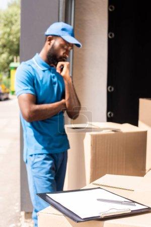 Photo pour Livreur afro-américaine, regardant les boîtes avec le presse-papier et un stylo sur le premier plan - image libre de droit