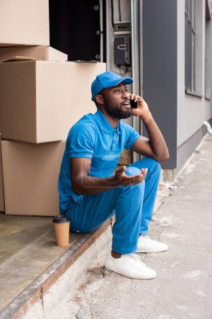 Photo for African american delivery man gesturing and talking by smartphone - Royalty Free Image
