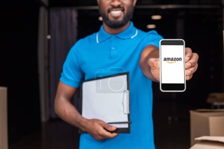 cropped image of african american delivery man showing smartphone with loaded amazon page