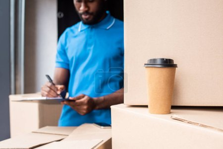 african american delivery man writing something to clipboard with coffee to go on foreground