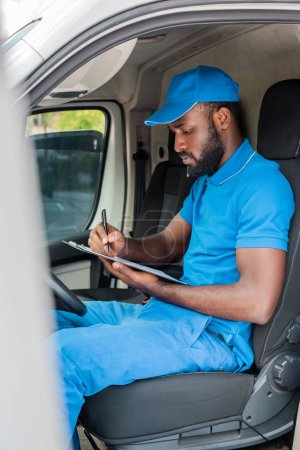african american delivery man writing something to clipboard in van