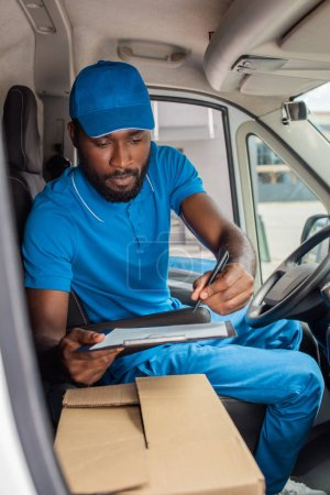 african american delivery man holding clipboard and pen in van