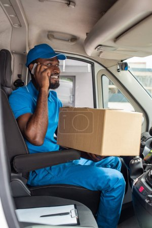 african american delivery man talking by smartphone in van