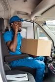 african american delivery man talking by smartphone in van