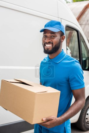 smiling african american delivery man carrying cardboard box