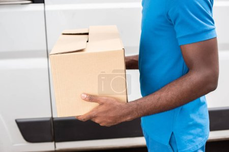 Photo for Cropped image african american delivery man carrying cardboard box - Royalty Free Image