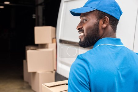 side view of smiling african american delivery man looking away