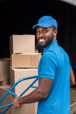 Photo for Smiling african american courier with cart looking at camera - Royalty Free Image