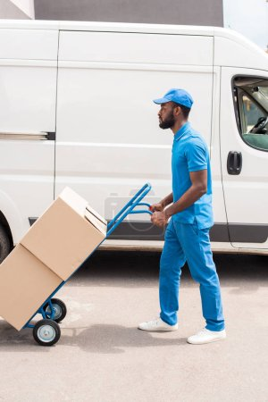 side view of african american delivery man with cart and boxes near van