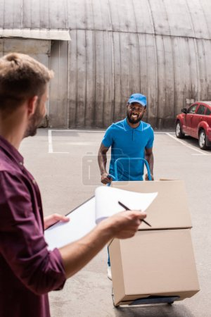 smiling african american courier with cart of boxes looking at client