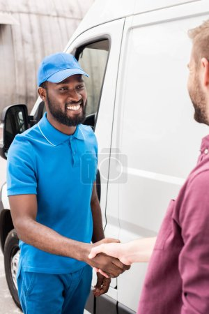 multicultural courier and client shaking hands near van