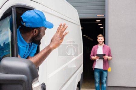 african american courier waving hand to client