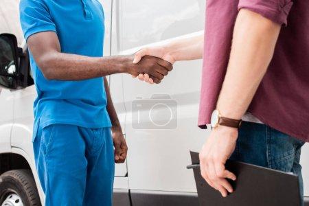 Photo pour Image recadrée de courier multiculturelle et client se serrant la main près de van - image libre de droit