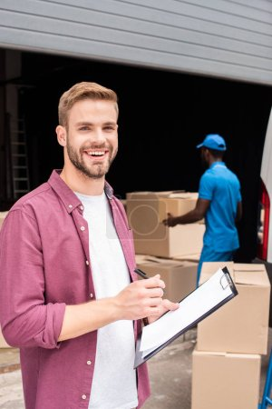 smiling caucasian customer of delivery service holding clipboard