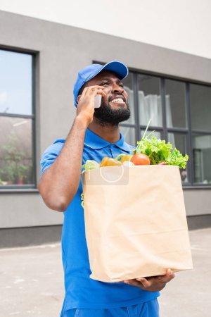 Photo pour Livreur afro-américaine tenant le sac en papier avec des légumes et de parler de smartphone - image libre de droit