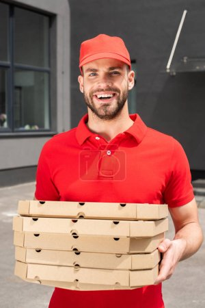 smiling caucasian courier holding boxes with pizza
